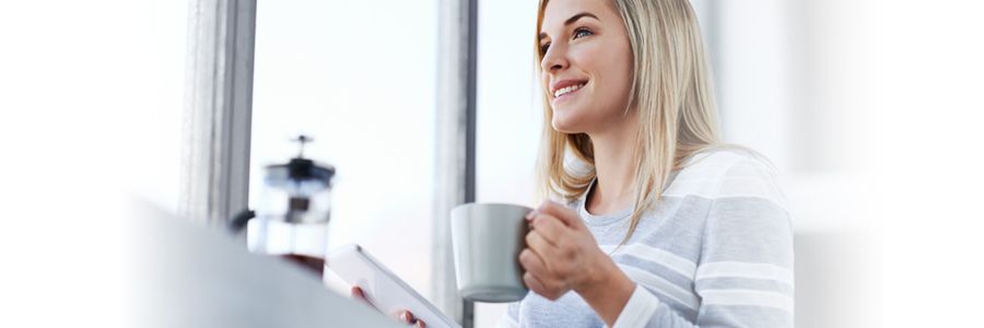 Smiling woman holding a white coffee mug and tablet